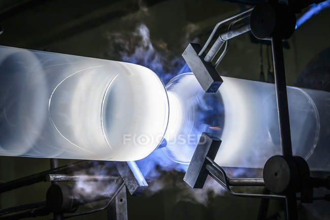 Large glass tube on lathe in glass factory — Stock Photo