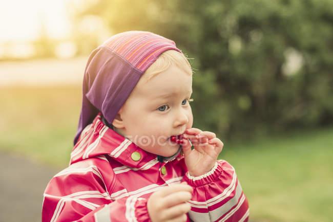 Молодая девочка ест красная смородина, на открытом воздухе — стоковое фото