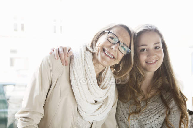 Портрет девочки-подростка и бабушки у окна кафе — стоковое фото