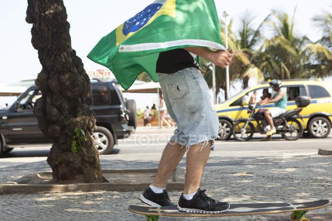 Jovem skate embrulhado em bandeira brasileira, Copacabana, Rio de Janeiro, Brasil — Fotografia de Stock
