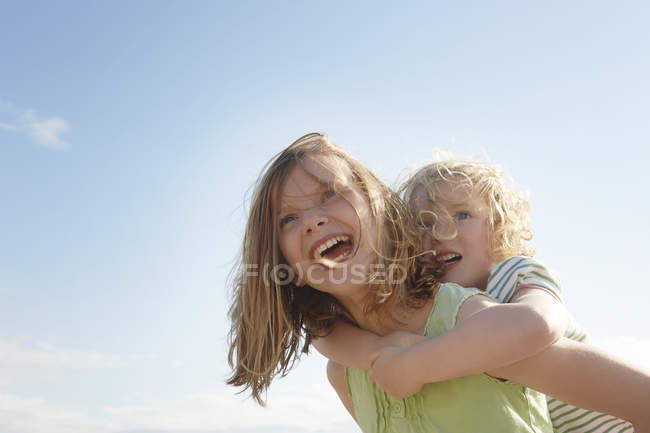 Low angle view of girl giving sister piggy back at coast — Stock Photo