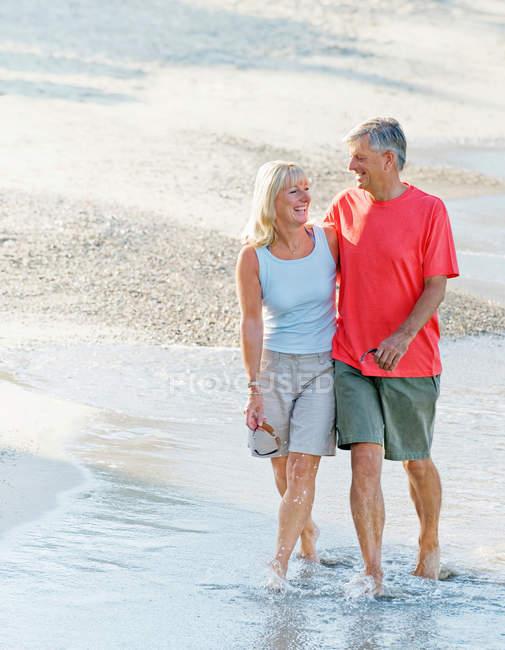 Coppia matura passeggiando lungo la spiaggia — Foto stock