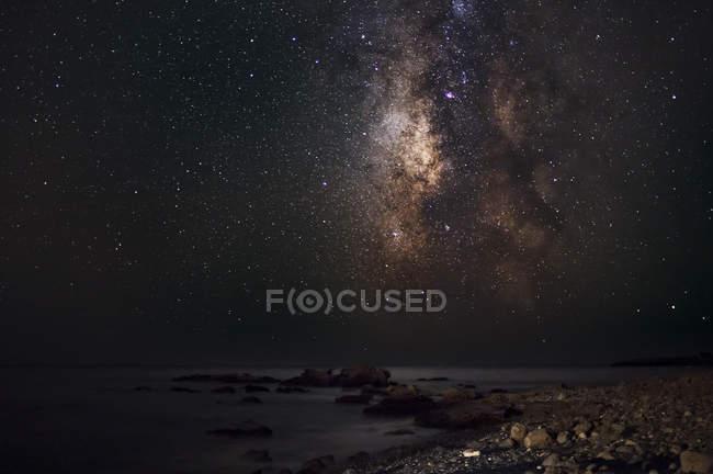 Milky way stars shining above ocean — Stock Photo