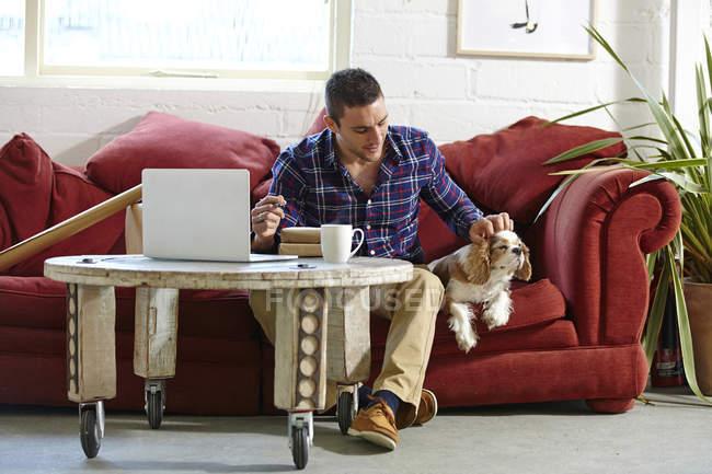 Взрослый мужчина пишет адрес на посылках, пока гладит собаку в рамке для фотографий — стоковое фото