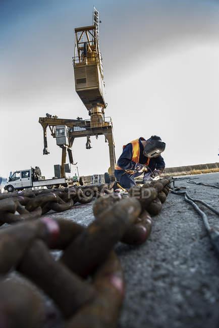 Зварювальник зварювального ланцюга на лаві підсудних пристані — стокове фото