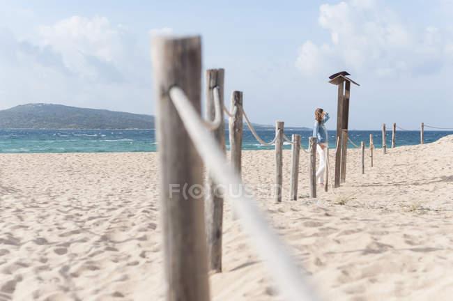 Mitte erwachsenen Frau liest Aushang am Seil eingezäunten Strand, Sardinien, Italien — Stockfoto