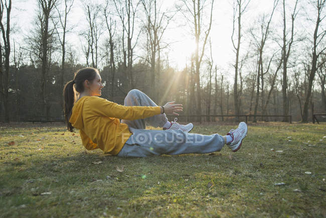Young female runner doing warm up sit ups — Stock Photo
