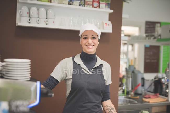 Female Barista working at cafe and smiling — Stock Photo