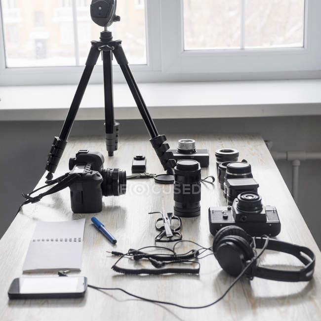 Smartphone and photography equipment on studio desk — Stock Photo