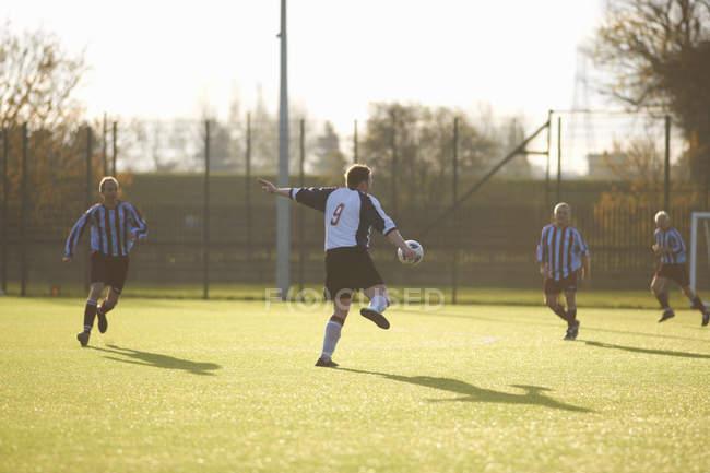 Fußballer kickt Ball auf feld — Stockfoto