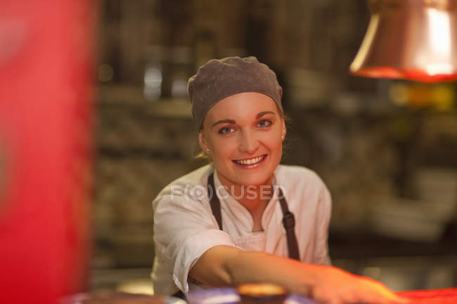 Portrait of young female chef serving over cafe counter — Stock Photo