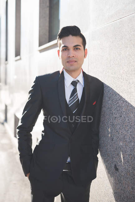 Молодой бизнесмен, прислонившийся к стене — стоковое фото