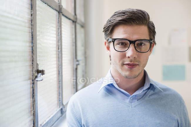 Porträt eines jungen Geschäftsmannes neben dem Bürofenster — Stockfoto