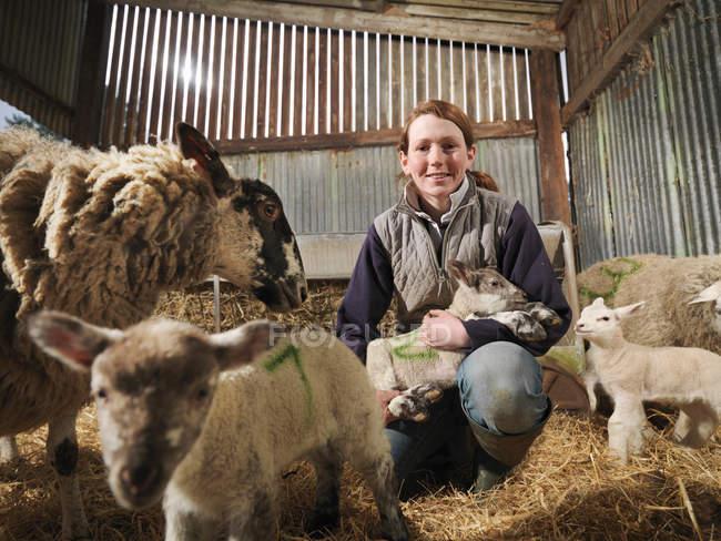Agriculteur femelle avec moutons et agneaux — Photo de stock