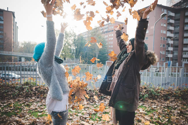 Two young women throwing autumn leaves in park — Stock Photo