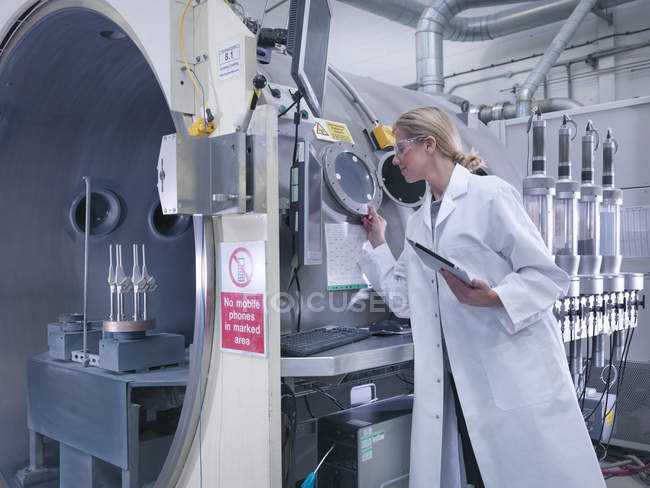 Female engineer with ceramic coating machine, coating artificial hip joints in orthopaedic factory — Stock Photo