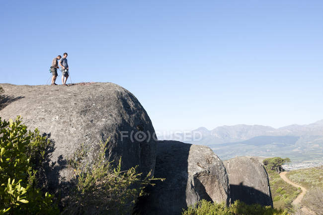 Young male climbers attaching ropes and harnesses on rocks — Stock Photo