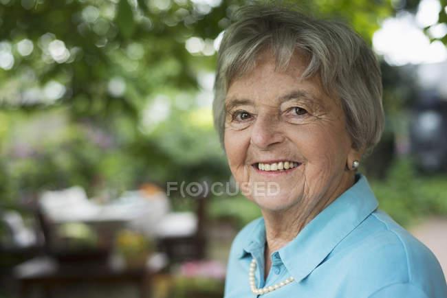 Retrato de mujer mayor en el jardín - foto de stock