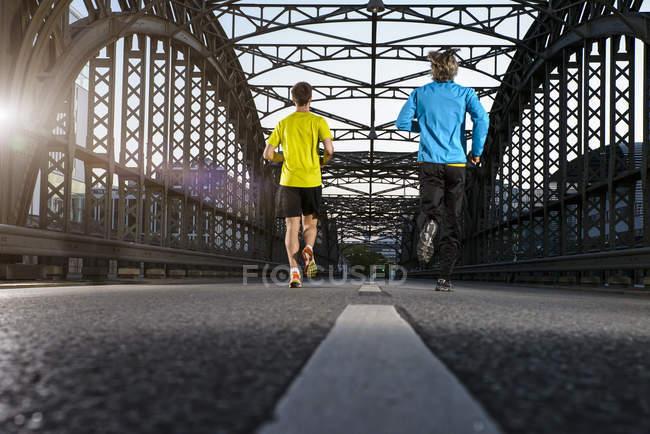 Friends jogging on bridge, Munich, Bavaria, Germany — Stock Photo
