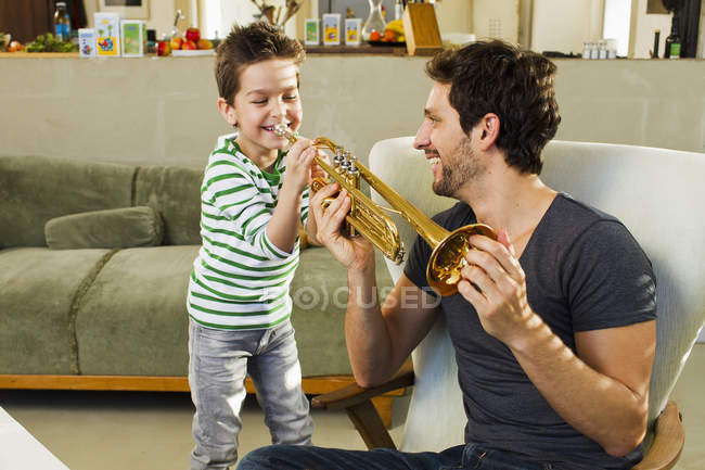Father encouraging little son playing trumpet — Stock Photo