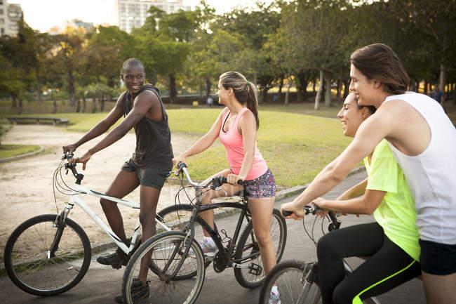 Jeunes adultes se préparant à faire du vélo dans le parc — Photo de stock