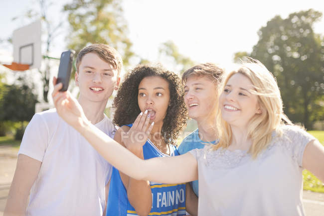 Four young adult basketball players taking smartphone selfie on court — Stock Photo