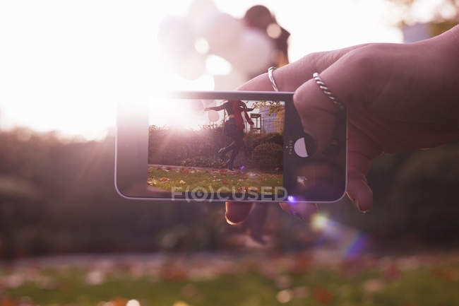 Hand holding camera, showing woman jumping — Stock Photo