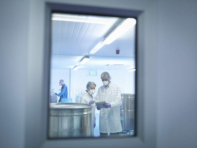 Workers using digital tablet in pharmaceutical factory — Stock Photo