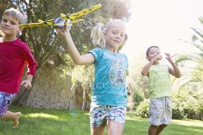 Três crianças correndo com avião de brinquedo no jardim — Fotografia de Stock