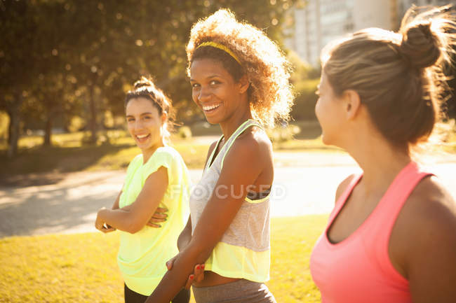 Three smiling young women training in  park — Stock Photo