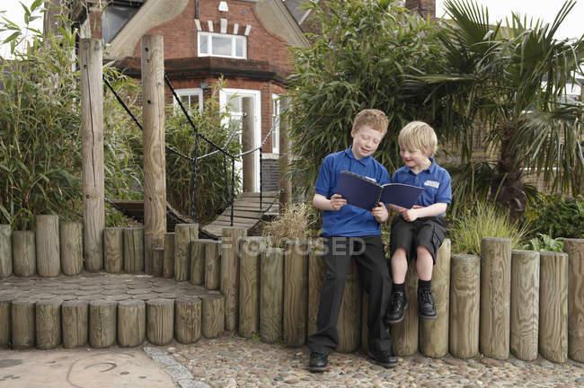 Dois meninos da escola lendo livro sobre cerca de log — Fotografia de Stock