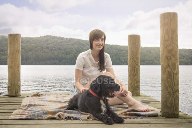 Junge Frau sitzt mit Haustier Terrier am Ende von einem Steg am See — Stockfoto