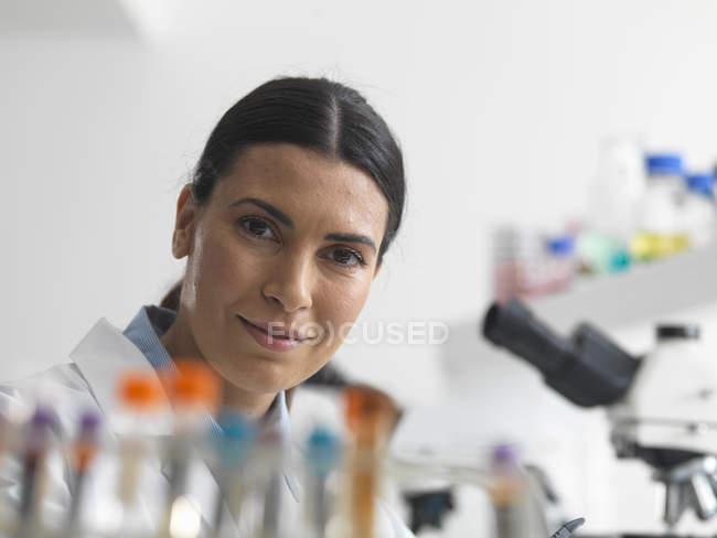 Женщина-исследователь в лаборатории рядом с микроскопом . — стоковое фото