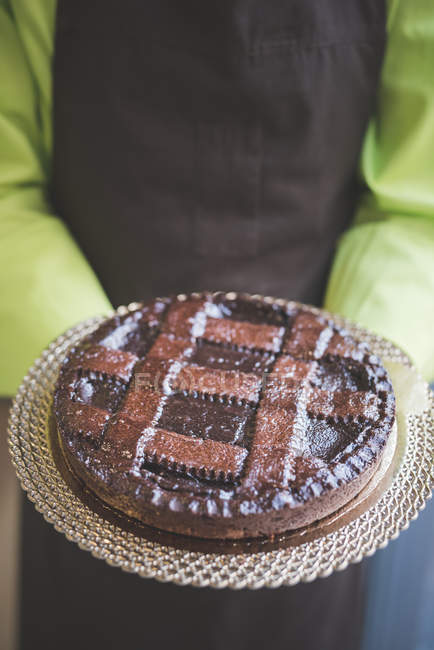 Maître d'hôtel portant la plaque de gâteau au chocolat, recadrée tir — Photo de stock
