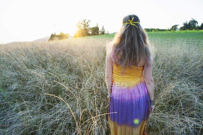 Vista posteriore della donna che indossa vestiti hippy e cammina attraverso il campo al tramonto — Foto stock