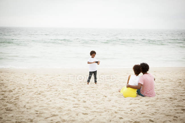 Couple and son taking photograph on beach — Stock Photo