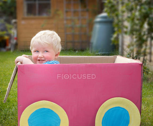 Young boy standing in cardboard box — Stock Photo