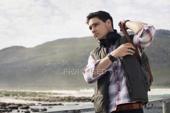 Молодой человек надевает рюкзак, Кейптаун, Западный Кейп, Южная Африка — стоковое фото