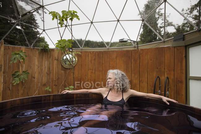Mature woman relaxing in hot tub at eco retreat — Stock Photo