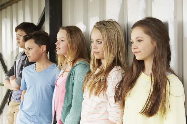 Ряд из пяти девочек и мальчиков, выглядывающих из укрытия — стоковое фото
