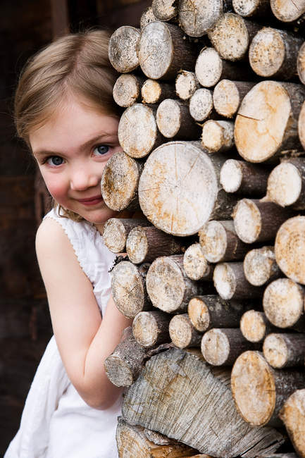Girl hiding behind logs. — Stock Photo