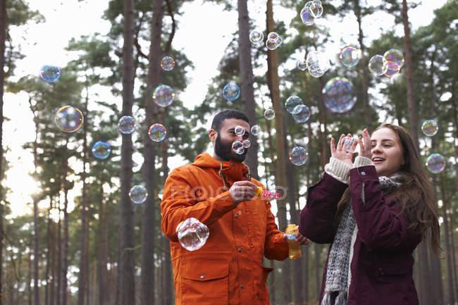 Pareja joven soplando burbujas en bosque - foto de stock