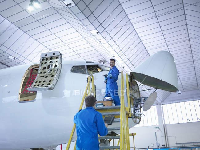 Инженеры, работающие над самолетами на авиаремонтном заводе — стоковое фото