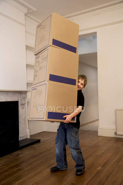 A boy holding a stack of three boxes — Stock Photo