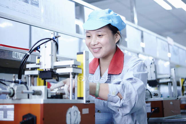 Female worker using equipment at e-cigarettes battery factory, Guangdong, China — Stock Photo