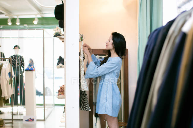 Side view of woman in changing room trying on clothes — Stock Photo