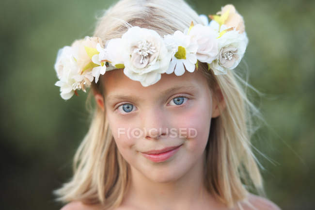 Portrait of girl with flower garland in her hair — Stock Photo