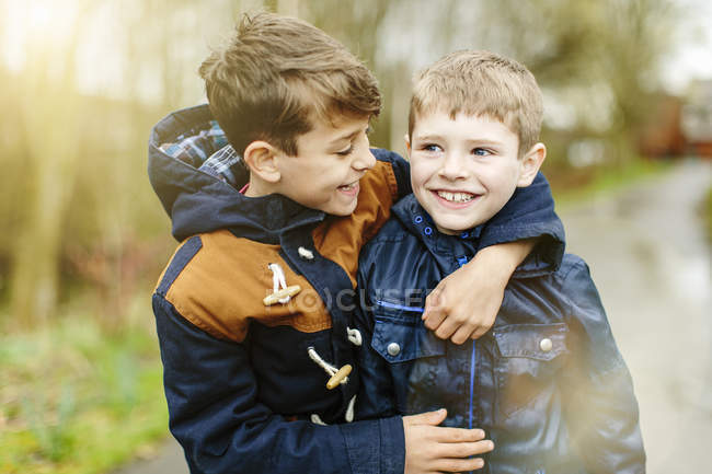 Pre-adolescent brothers in jackets hugging outdoors — Stock Photo