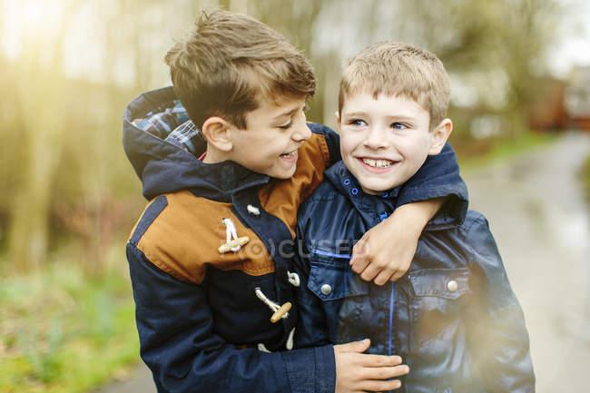 Братья-подростки в куртках обнимались на улице — стоковое фото