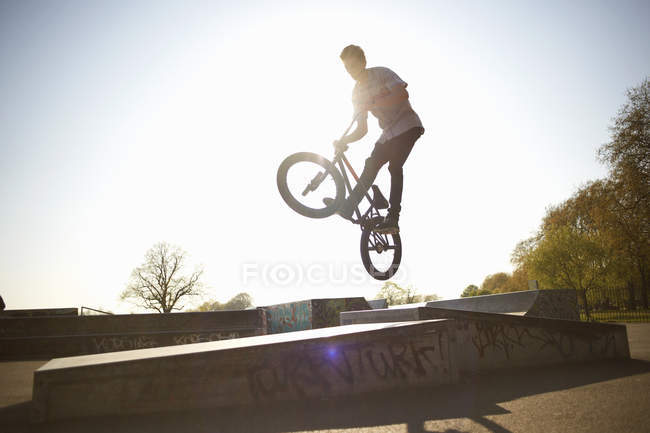 Young man, in mid air, doing stunt on bmx at skatepark — Stock Photo